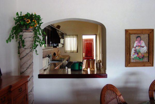 На этом фото в дизайне кухни используется два окна - раздаточное и межкомнатное
