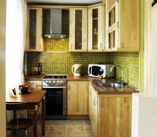 Деревянная мебель в сочетании с оливковым цветом дополнит интерьер маленькой кухни