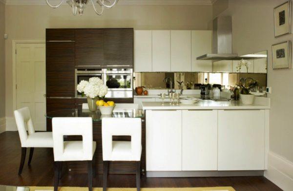 Стеклянный стол-полуостров отлично впишется в дизайн кухни маленькой студии