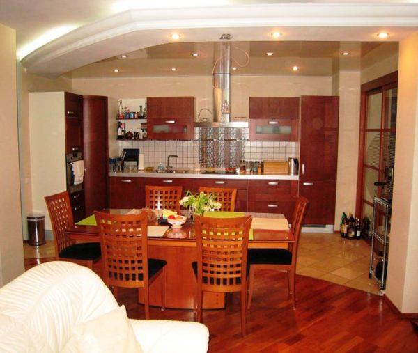 На этом фото показано разделение кухонной зоны и гостинной за счет разного покрытия полов