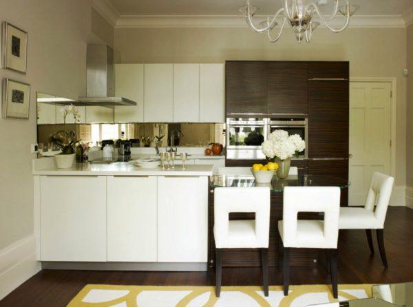 На этом фото в дизайне маленькой кухни показано оформление фартука зеркальными обоями