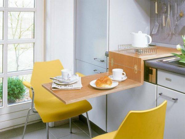 Самый бюджетный вариант стола для маленькой кухни – складная модель (по типу столиков в поездах). Конструкция изделия незатейлива и ее можно сделать самостоятельно по индивидуальным размерам