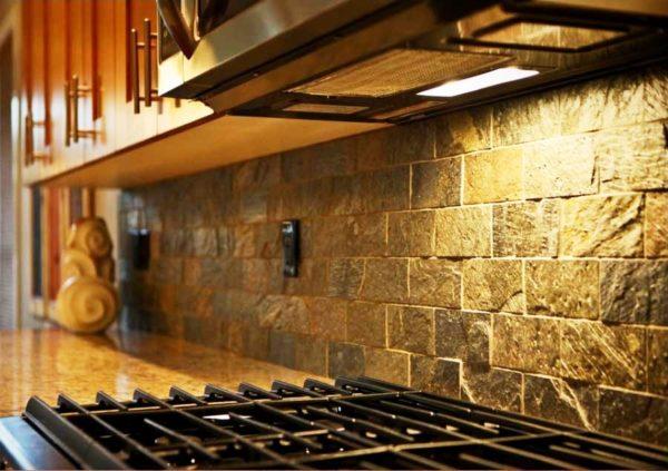Можно оформить стену у раковины и плиты с помощью камня