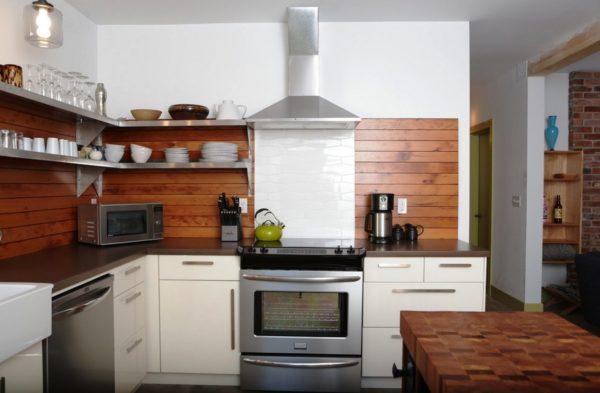 Оригинальный интерьер кухни с деревянным фартуком для защиты стен в зоне приготовления пищи