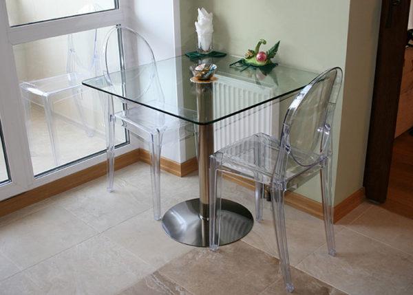 стол из стекла на тонких ножках на маленькой кухне