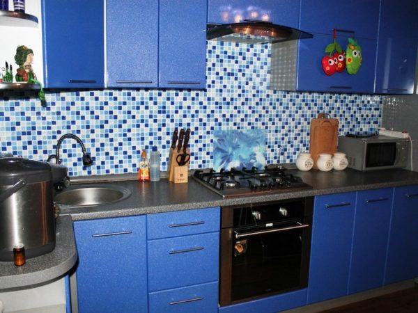 Фартук синего цвета будет хорошо сочетаться с рабочей поверхностью белого, серого или черного цвета